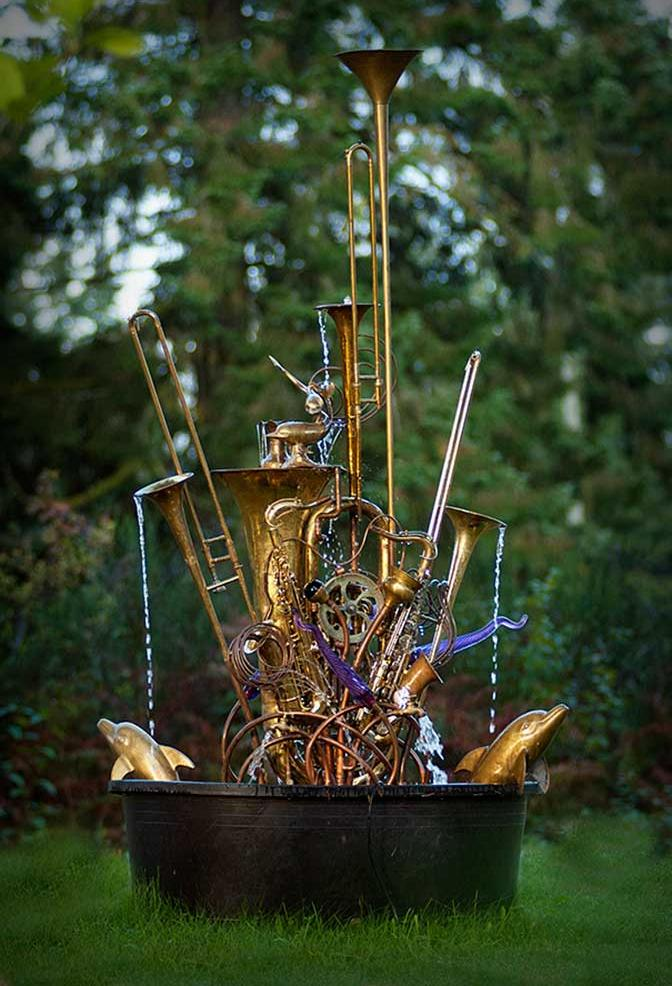 Musical instrument fountain sculpture created with copper tubing, a water wheel, blown glass, repurposed brass and silver, and upcycled musical instruments including a tuba, trombones, trumpets and flutes.