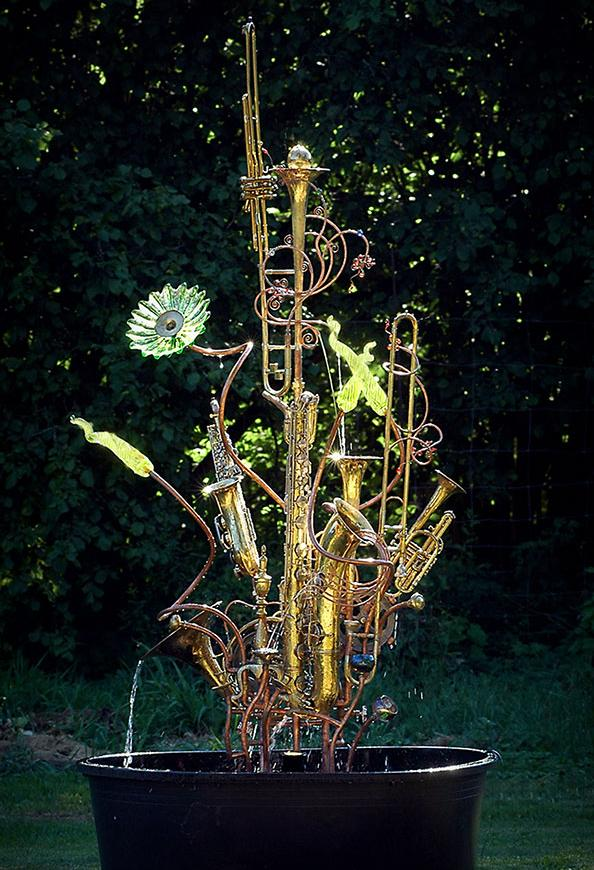 Musical instrument fountain sculpture constructed from copper tubing, a bicycle wheel, blown glass, repurposed brass and silver, and upcycled musical instruments including a trombone, tubas and trumpets.
