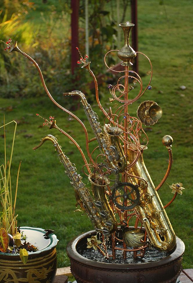Musical instrument fountain sculpture made from copper tubing, a water wheel, repurposed brass and glass, and upcycled musical instruments including an alto sax, a tenor sax, and a baritone sax.
